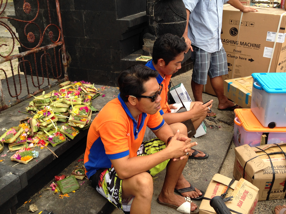 Daily life in Lembongan: Offerings in the background. Checking phones in the foreground.