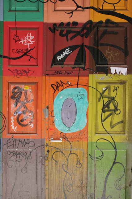 """Just four doors down from me, I have taken a liking to this piece of colourful art (despite the graffiti). The caption in blue in the middle says """"Estoy solo"""" (I am solo)."""