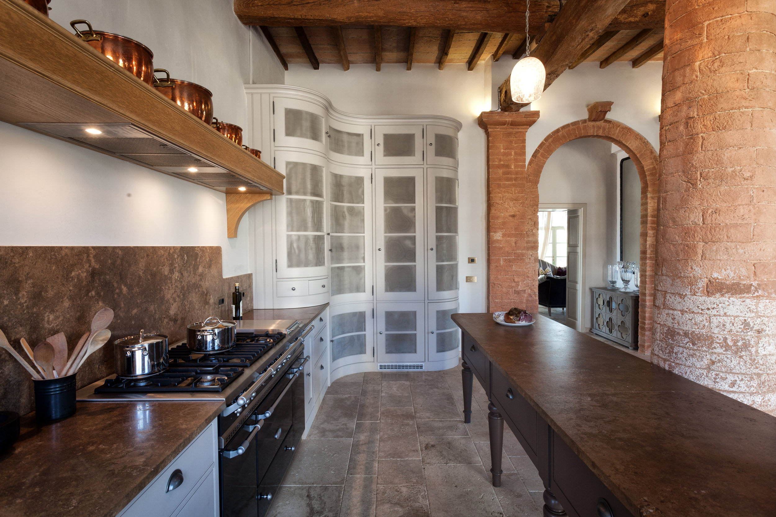 The elegant curved tall cupboards sit perfectly with the huge stone pillars in the kitchen