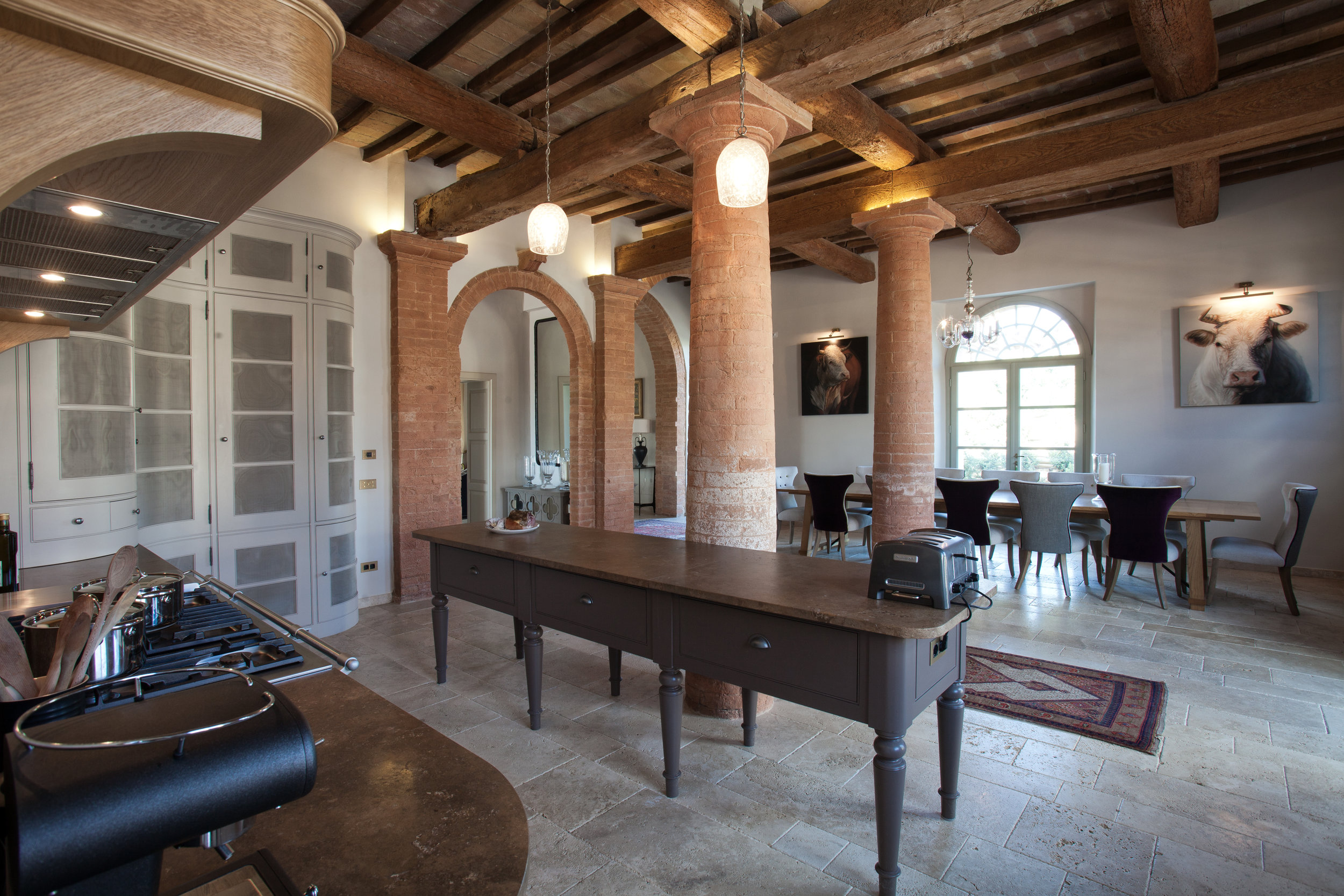 The kitchen and dining area are separated by old brick pillars