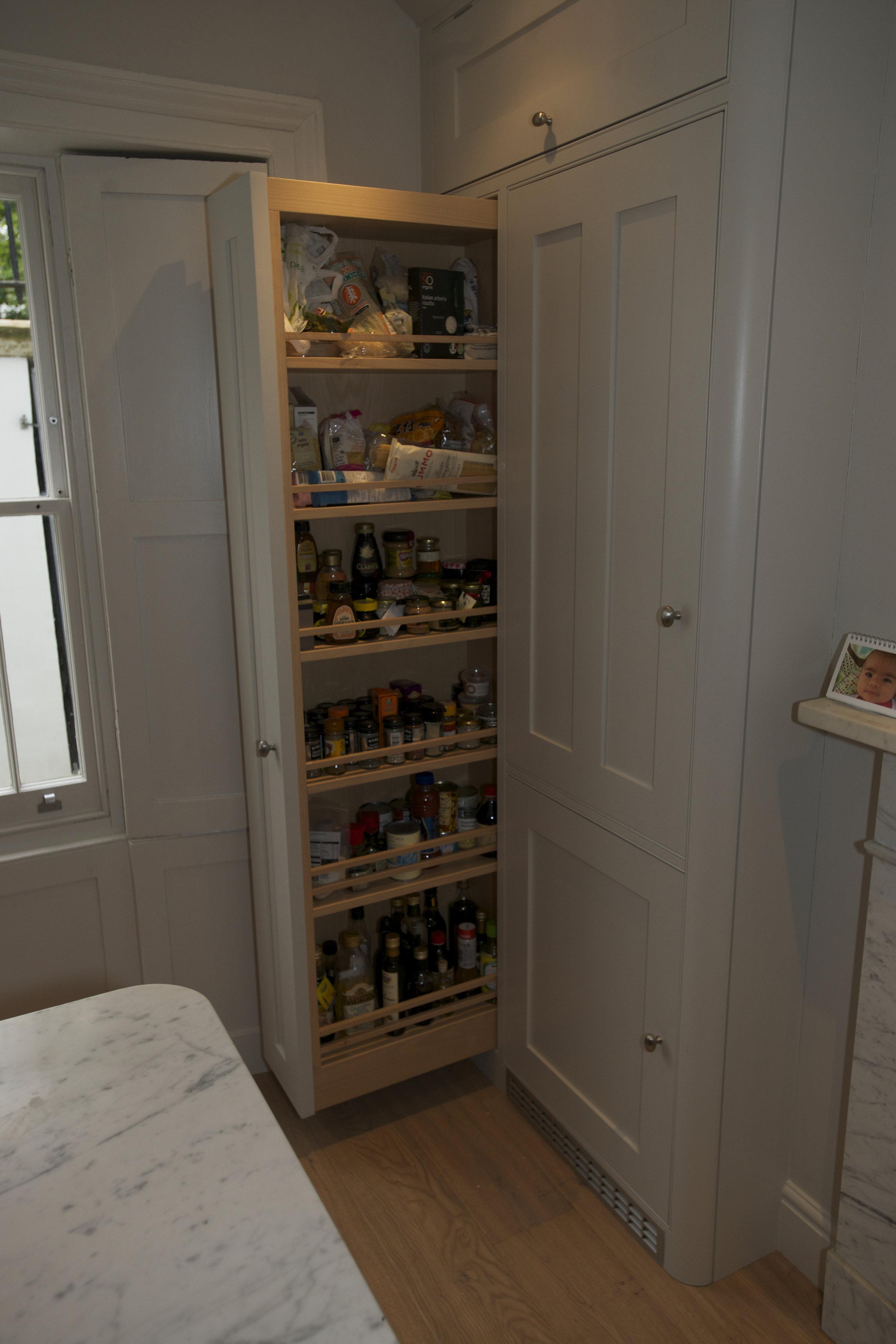 Pull out oak spice racks sit alongside the in built fridge freezer