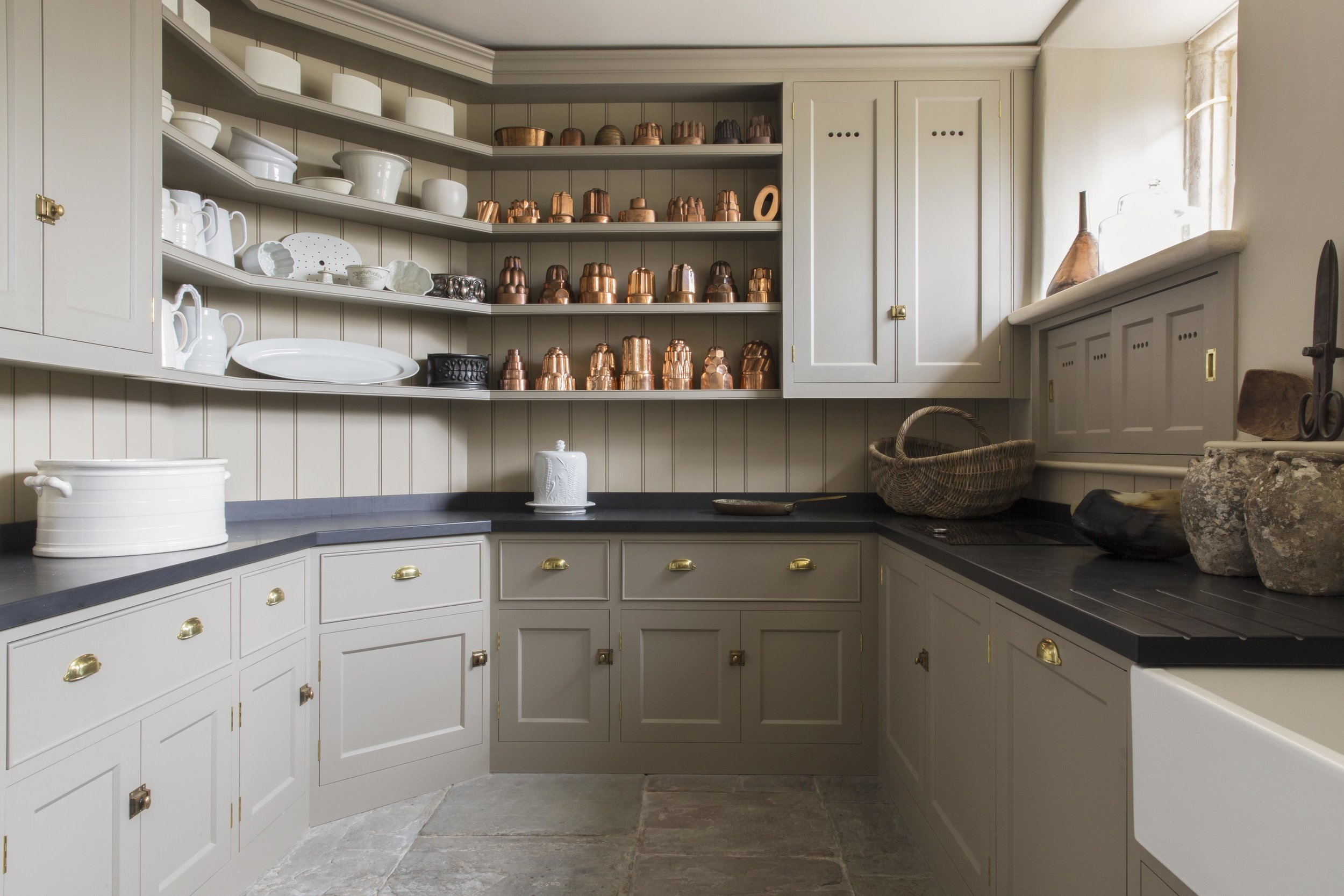The natural tones of the paintwork and large York stone slabs act as a wonderful foil for this impressive collection of jelly moulds.