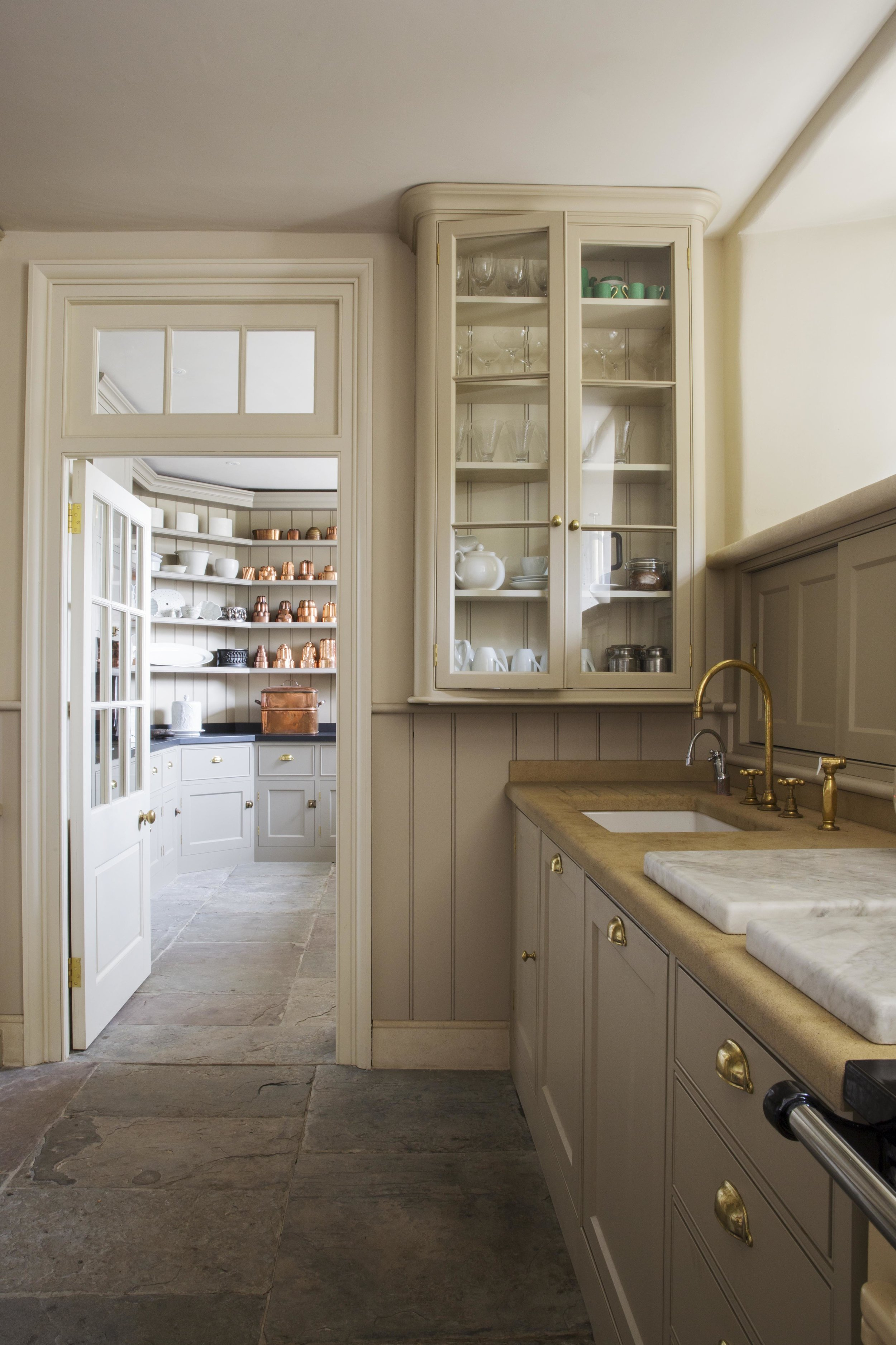 Tall, elegant glazed cupboards reach up to the ceiling and frame the doorway.