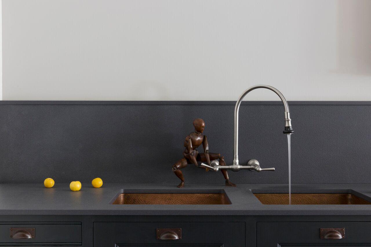 Double copper sinks contrast with a matt textured worktop