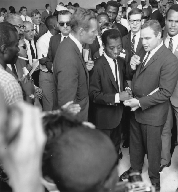 Photo courtesy of U.S. Information Agency. Press and Publications Service. A work of public domain. B&W photo of Civil Rights March on Washington D.C. 28 August, 1963. James Baldwin is smiling & centered in a large crowd next to Charlton Heston & Marlon Brando, Sydney Poitier can also be seen in the crowd. | The Naked Page