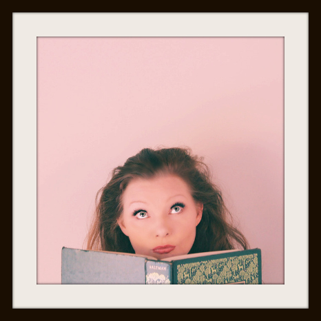 Blissom looks up from green book. Pink background in a frame. | The Naked Page