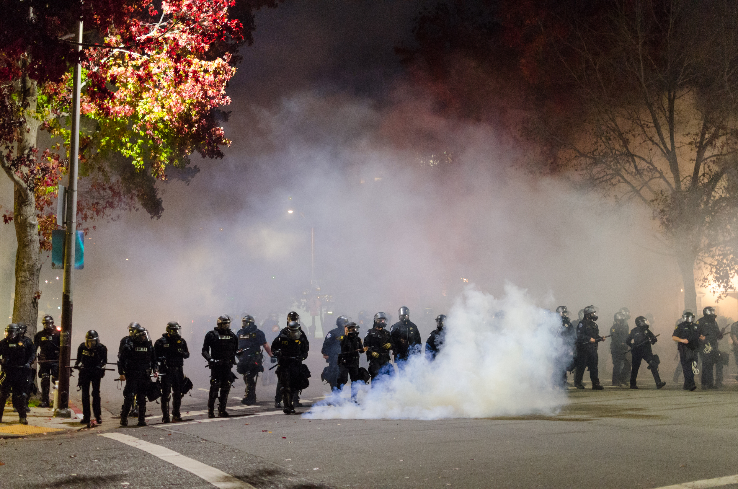 Line of gas masked police marching through tear gas towards a crowd of fleeing protesters on December 6th, 2014 in Berkeley, CA - photo by Kyle Cameron