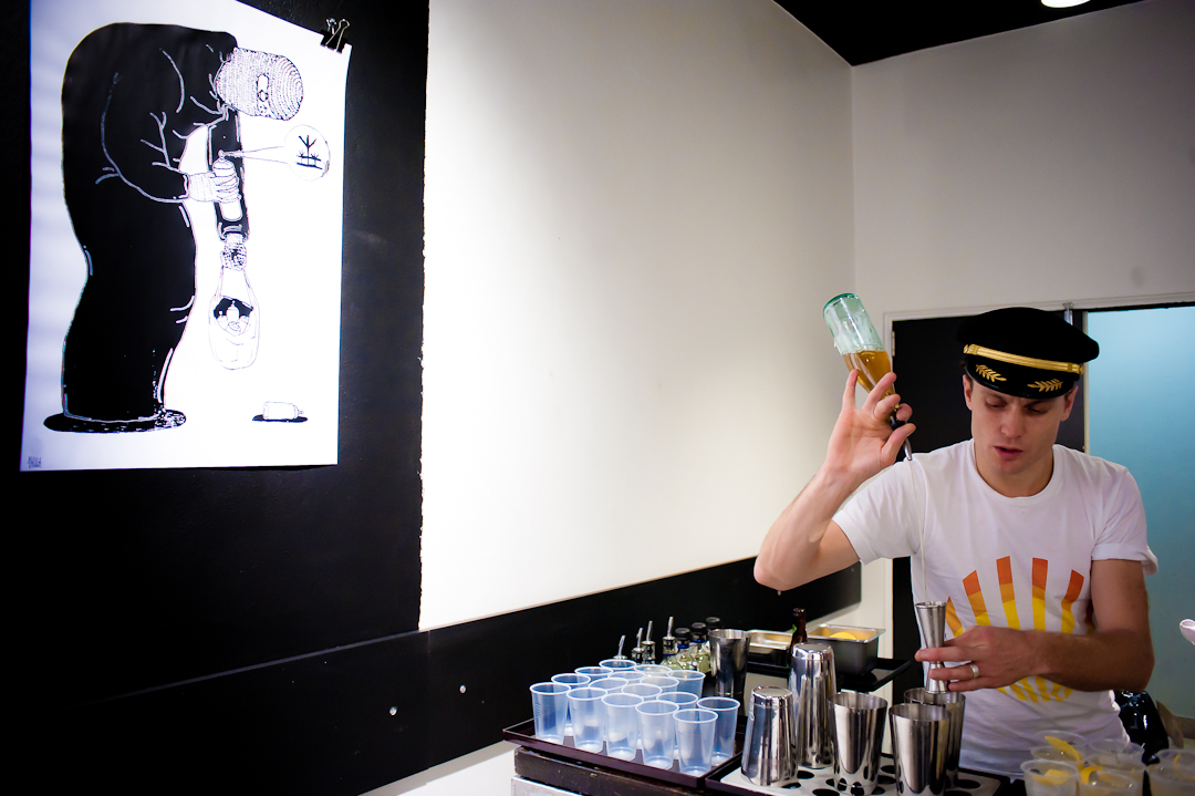 Christopher Thomas mixing cocktails in front of some artwork