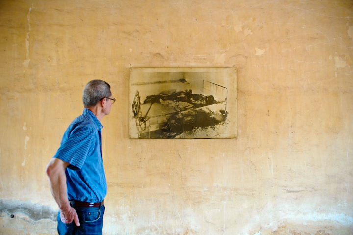 Dan Southerland looks at a photo on the wall of Phnom Penh's Tuol Sleng genocide museum.