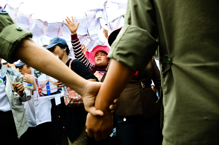Police lock hands to block protesters from coming near a courthouse where broadcaster Mam Sonando was being sentenced to 20 years in prison.