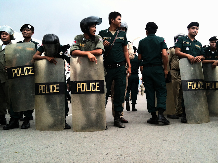 Police with riot shields wait near supporters of jailed broadcaster Mam Sonando.
