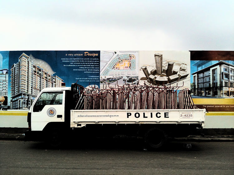 A police vehicle is parked in front of advertisements for a building development near where supporters of broadcaster Mam Sonando were protesting in central Phnom Penh.