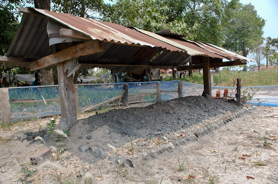 The grave of former Khmer Rouge leader Pol Pot sits near a dirt road off the main highway. It is a makeshift affair, lined with old soda bottles under a tin roof. Villagers come here to pray for good luck and peace.