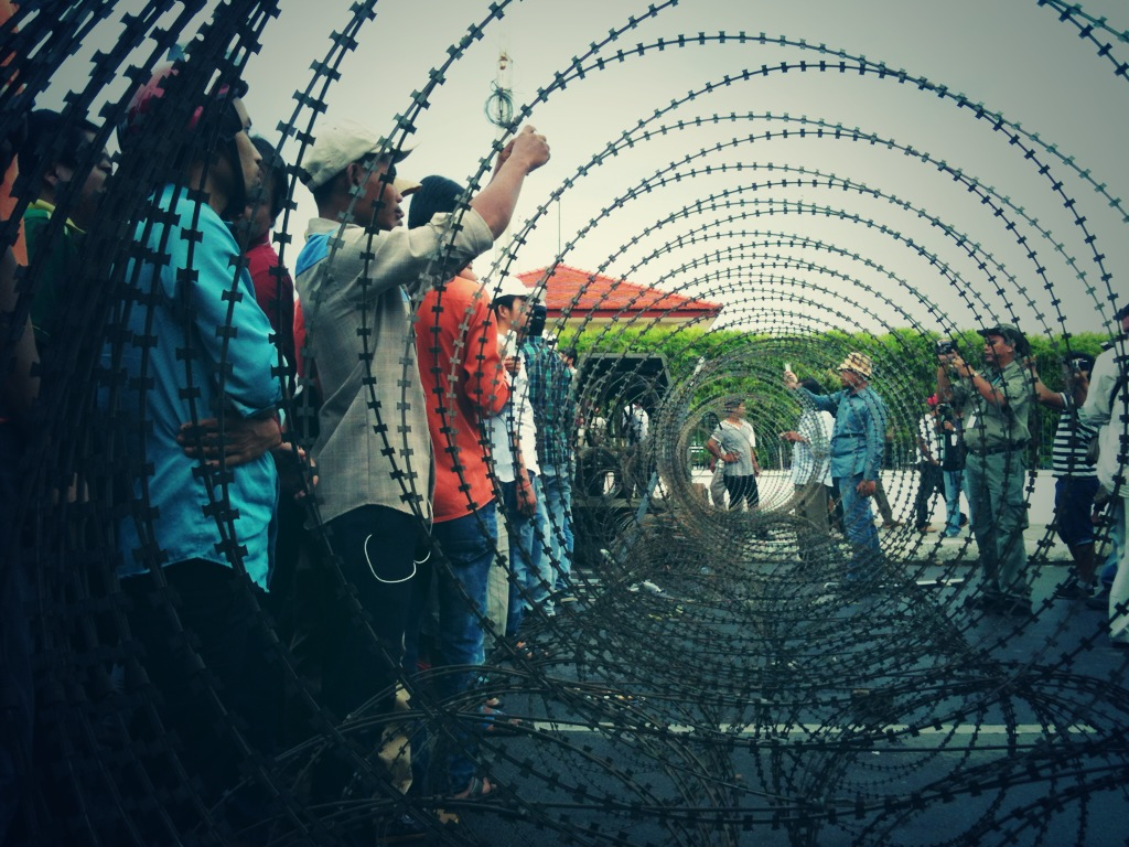 Protesters gather on one side of a barbed wire barricade on Phnom Penh's riverside.