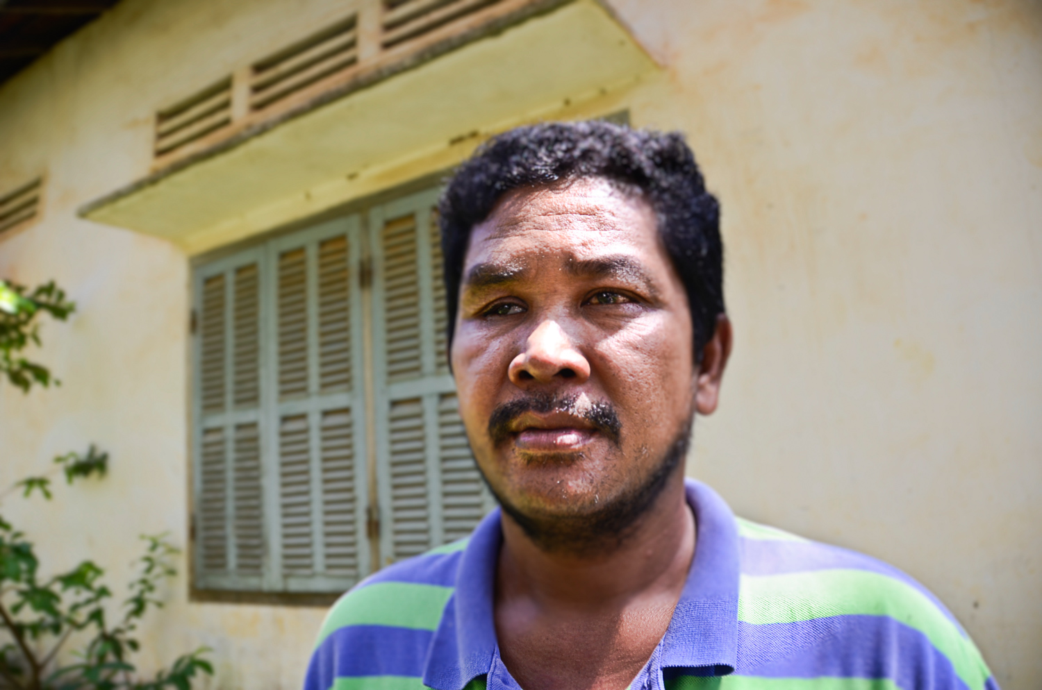 Khoem Sarom stands near his home outside Cambodia's capital, Phnom Penh. He has been searching for his niece ever since the pair was separated after the Khmer Rouge fell from power.