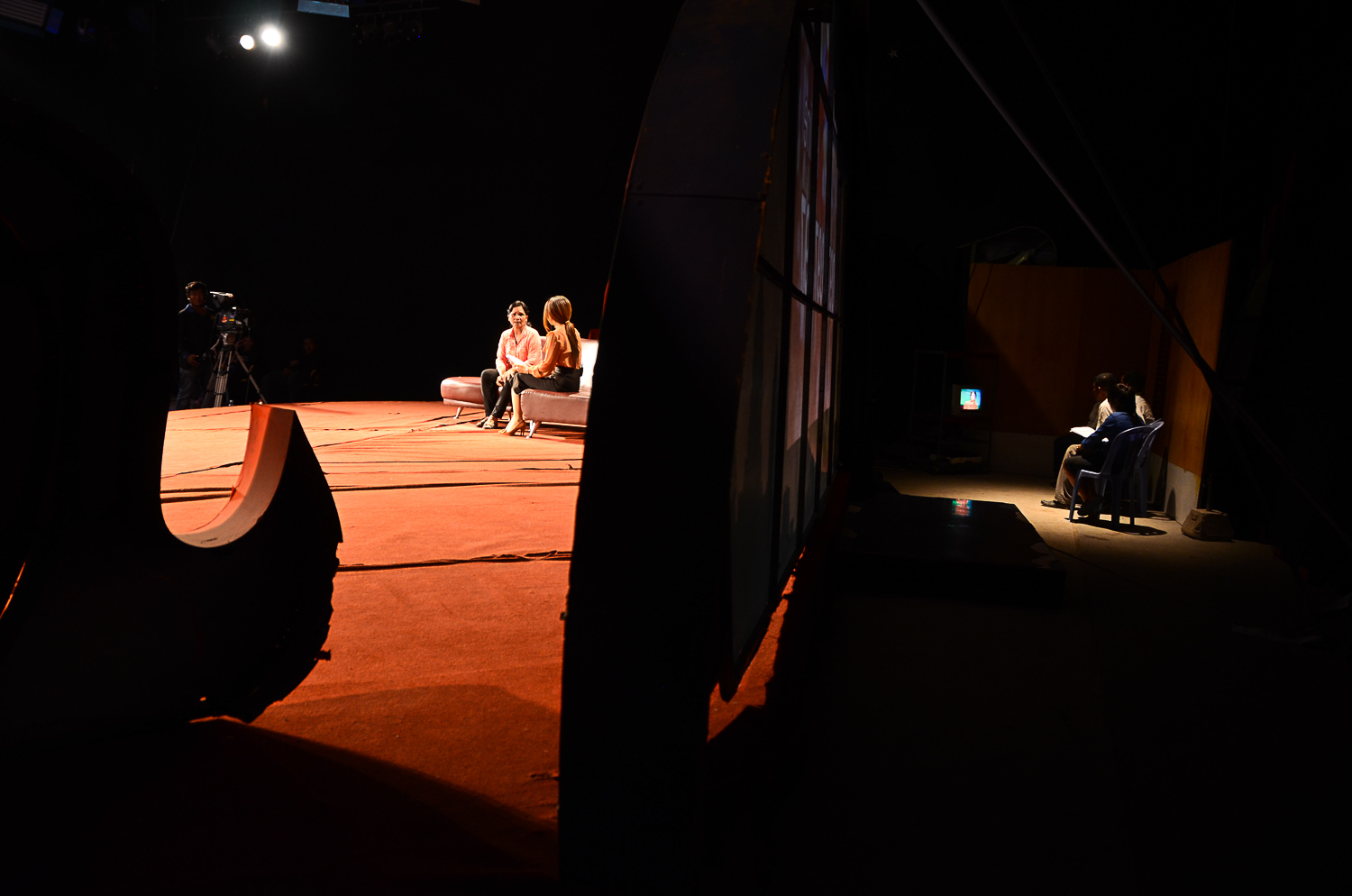 Seak Mala, left, sits on stage with the show's host, her uncle, Khoem Sarom, waits backstage with his family. The pair have not seen each other in almost 35 years.