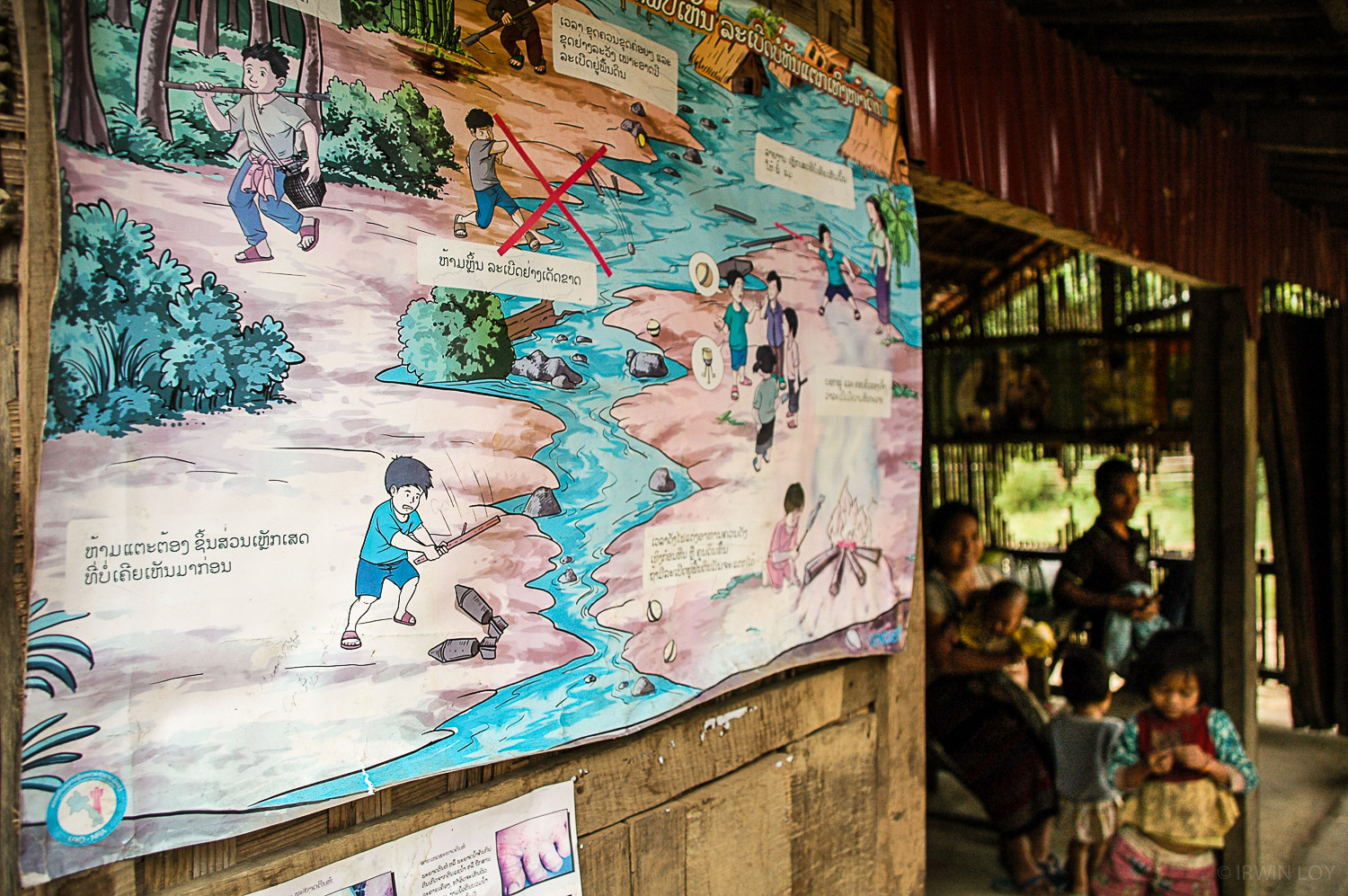 A poster warns of the dangers of buried cluster bombs and other munitions in a village in Sekong, Laos.