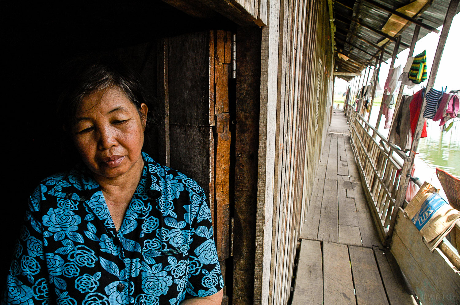 Yuen Mach, 58, stands in the doorway to her home over Phnom Penh's Boeung Kak lake. Her family is one of roughly 4,000 that could be forced to move to make way for a controversial 133-hectare real estate project.