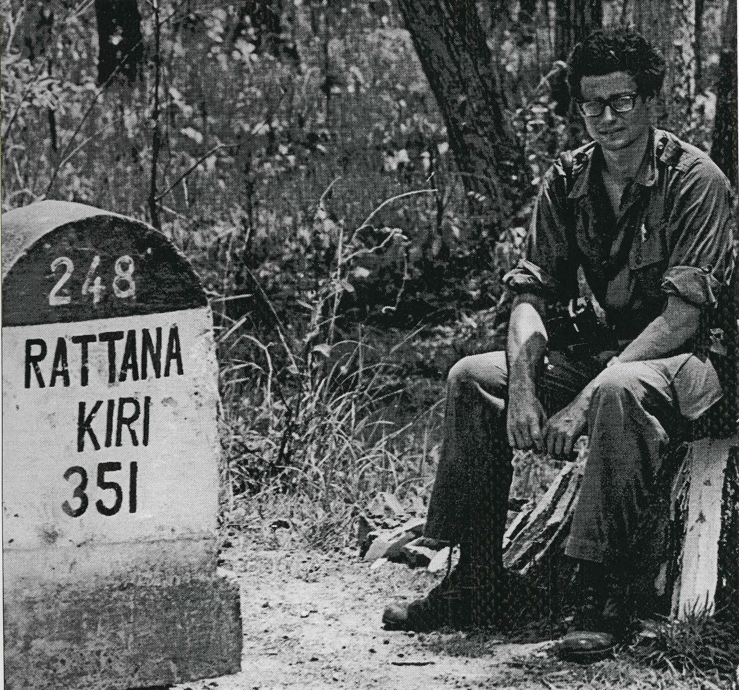 A photo of Dan Southerland taken during the war. He's sitting beside a highway marker noting the distance to Ratanakkiri province in northeast Cambodia.
