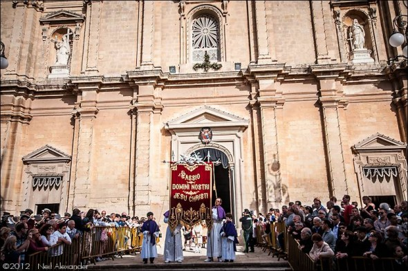 The Passion of Our Lord Jesus Christ banner leaving St. Catherines church as part of the Good Friday parade Zejtun Malta complete with TV cameraman