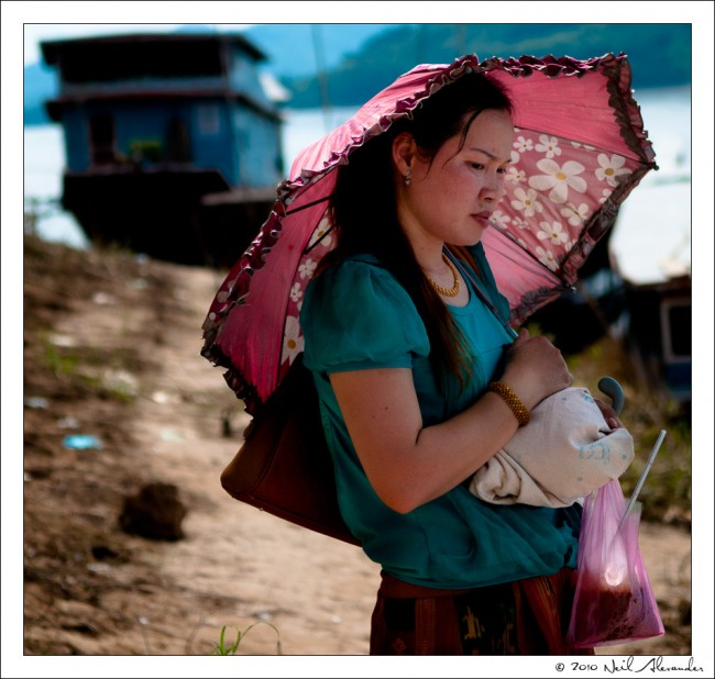 L aotian woman waiting for a boat on the side of the Makong River, Luang Prabang, Laos by Neil Alexander