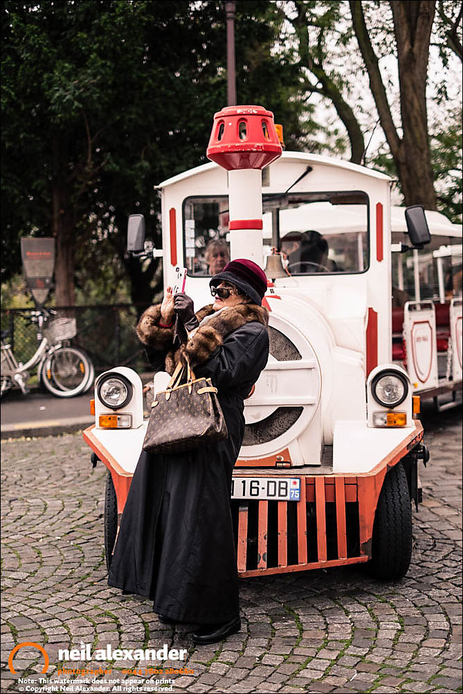 A woman taking a photograph near Sacr�-Coeur, Paris
