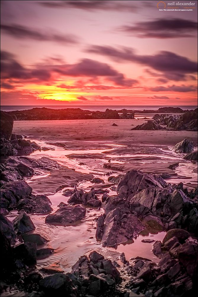 A long exposure of the sun setting over Rhosneigr beach with rocks in the foreground