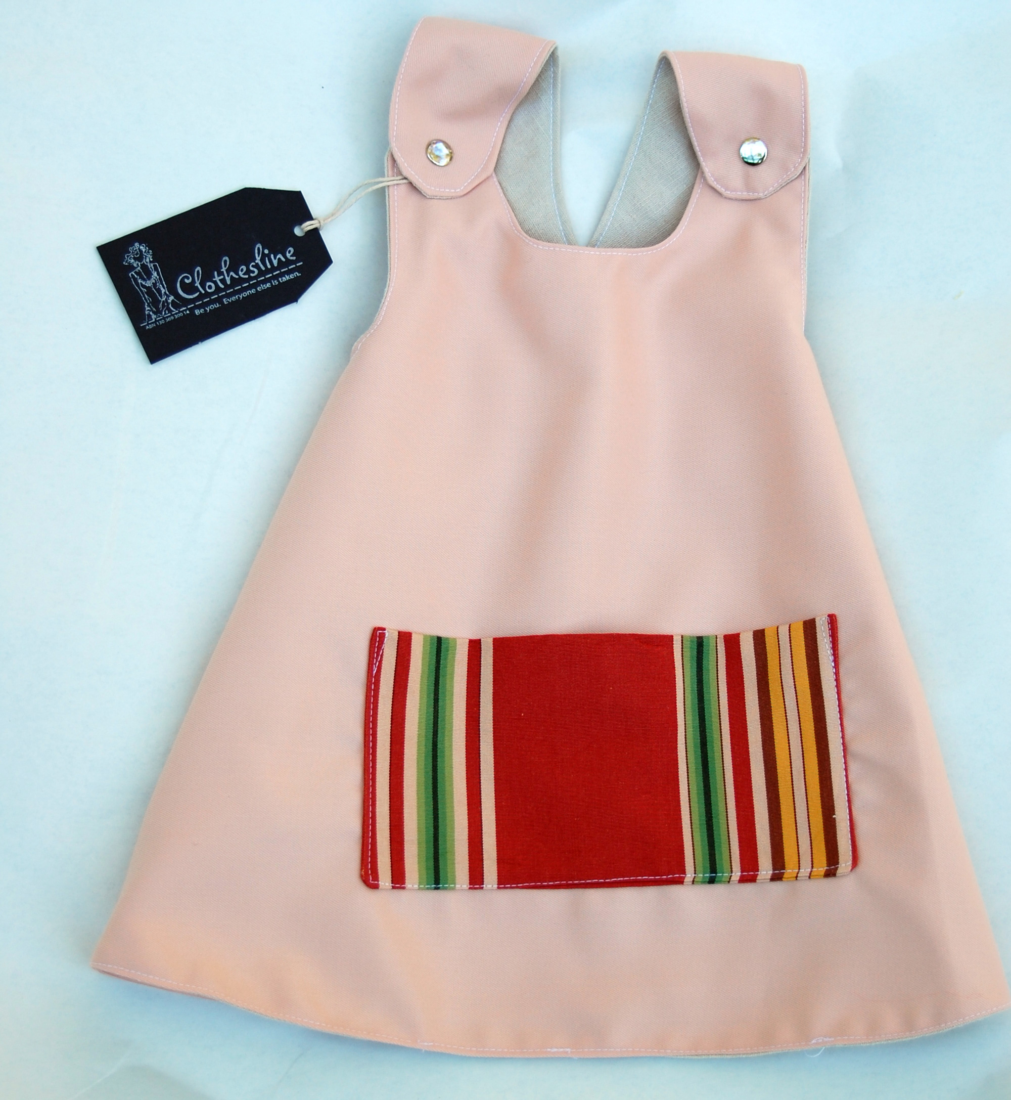 Sweet apron dress for a one-year-old. Pocket upcycled from some upholstery fabric samples. It's reversible too for when you spill stuff on the front!