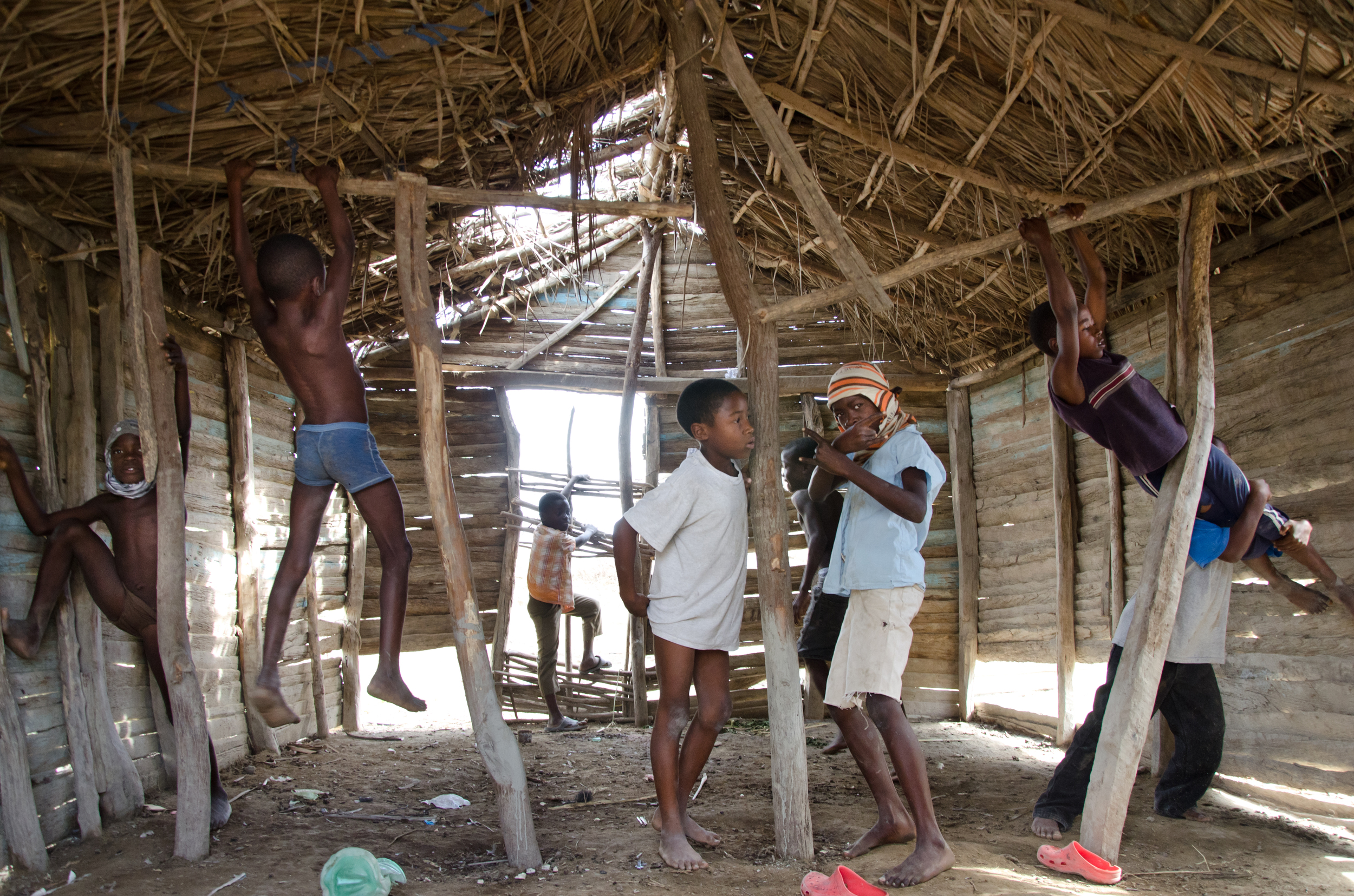 ​Boys from a Haitian sugar cane shanytown play in an abandoned thatch hut near Barahona, Dominican Republic.
