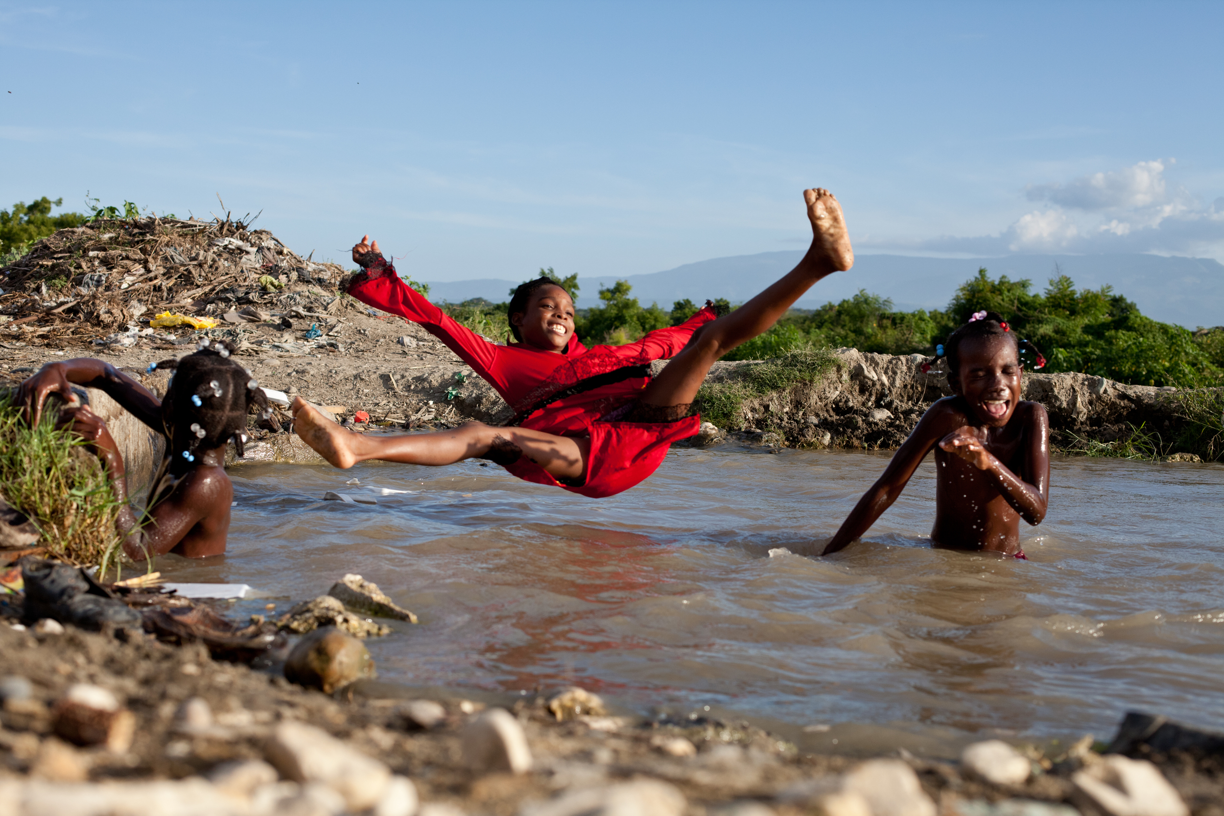 ​Girls from a Haitian sugar cane farming community play in a dirty irrigation ditch at sunset near Barahona, Dominican Republic.