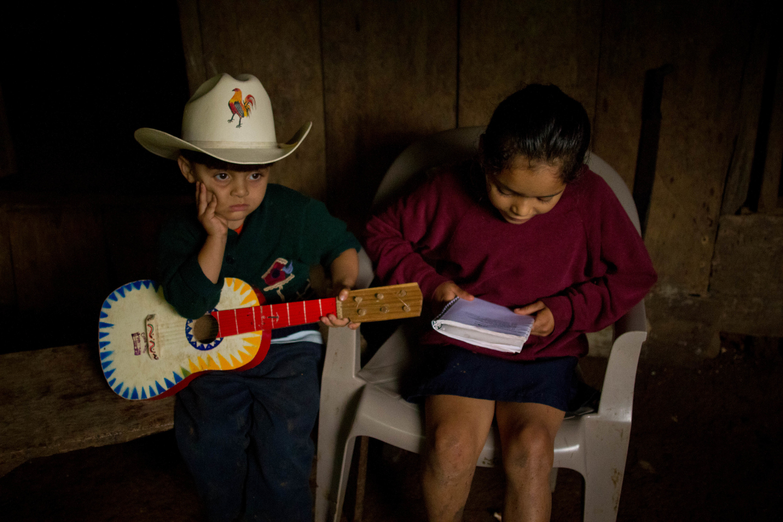 ​Elder, 3, and his cousin Angela, 8, trapped beneath the porch roof on a cold, rainy day in El Roblar, Nicaragua.
