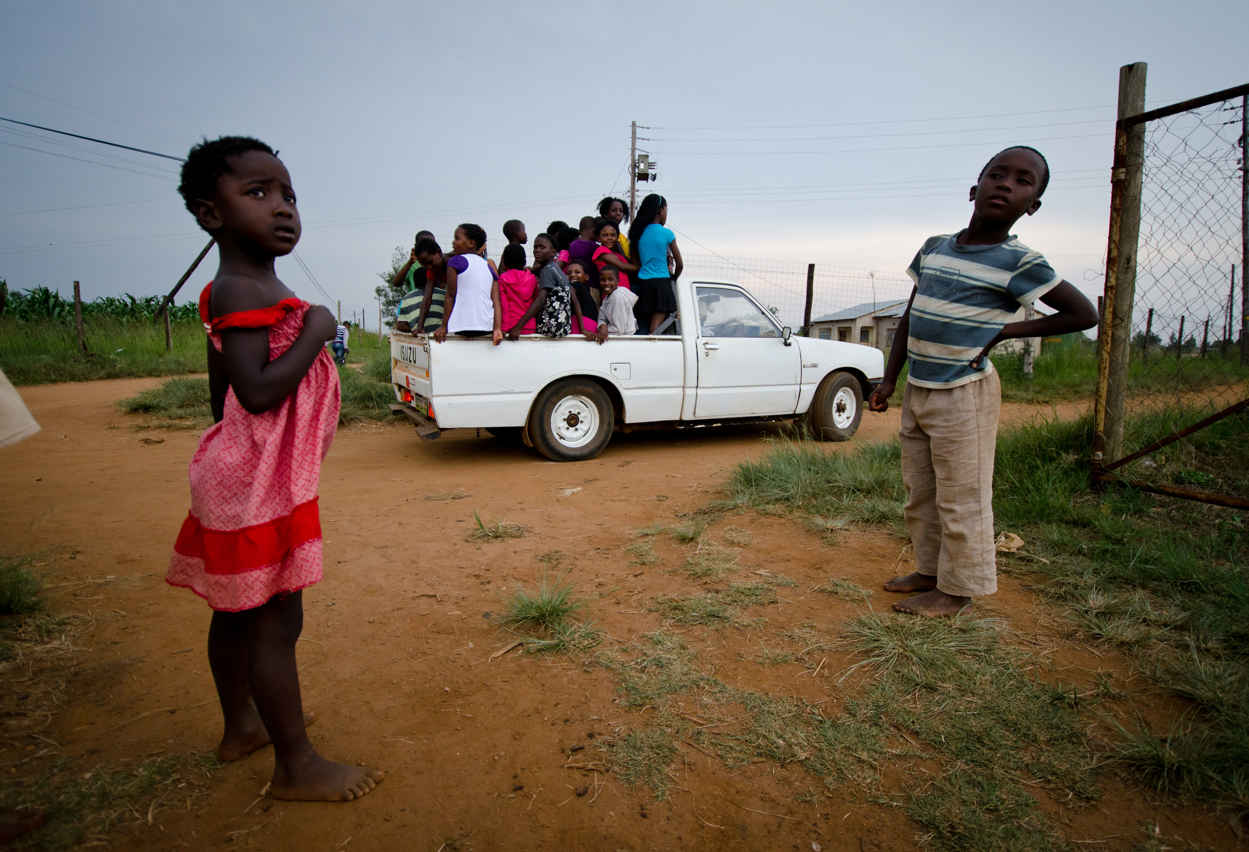 Children in rural Swaziland catch a ride home from Bible club in the back of a pickup truck.