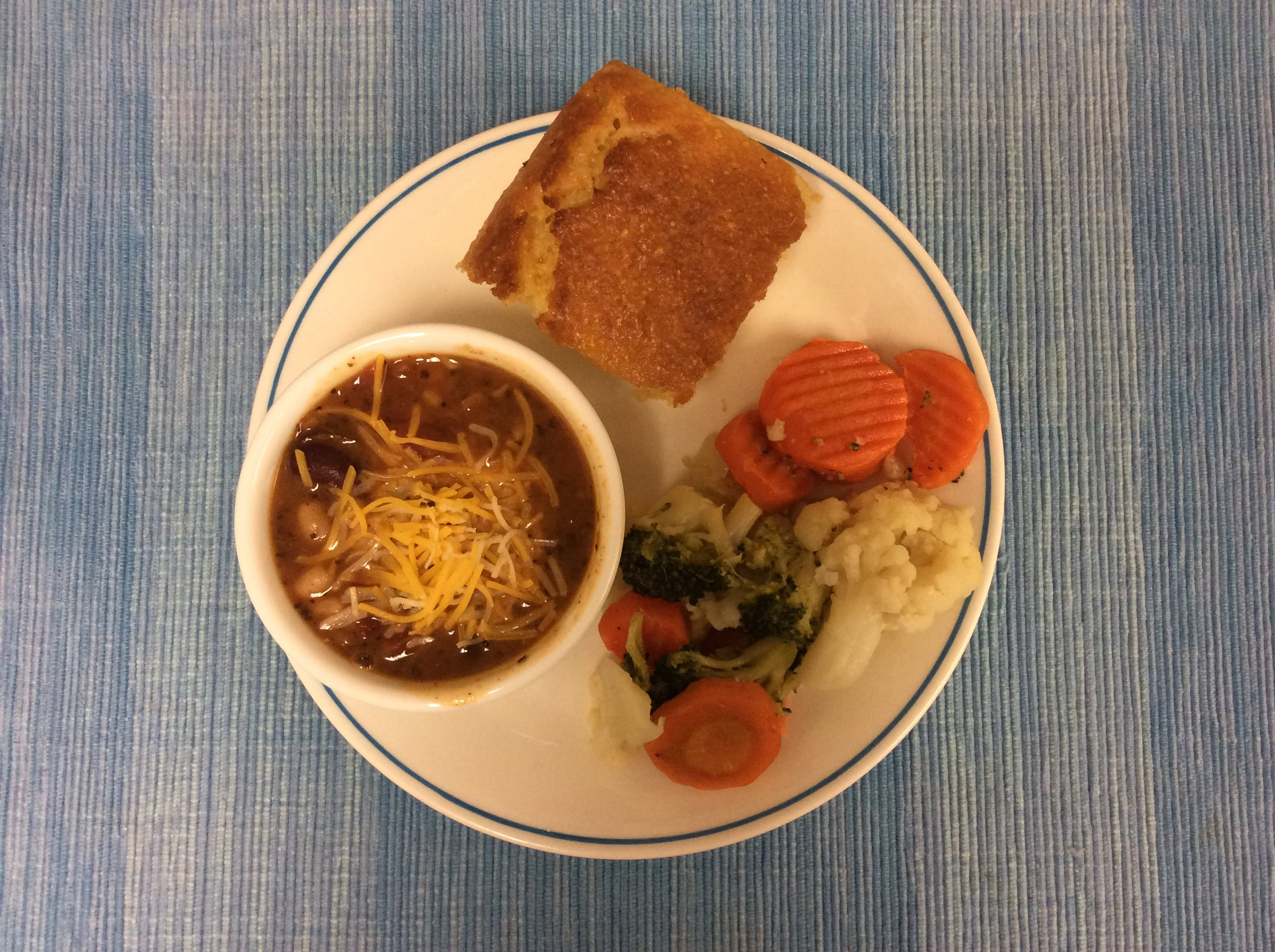 Vegetarian Chili with Cheddar Cheese, California blend vegetables, and honey cornbread