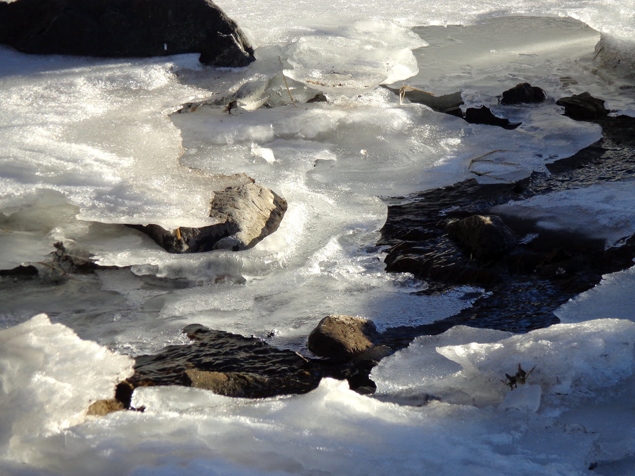 water-running-under-melting-ice-on-stream.jpg