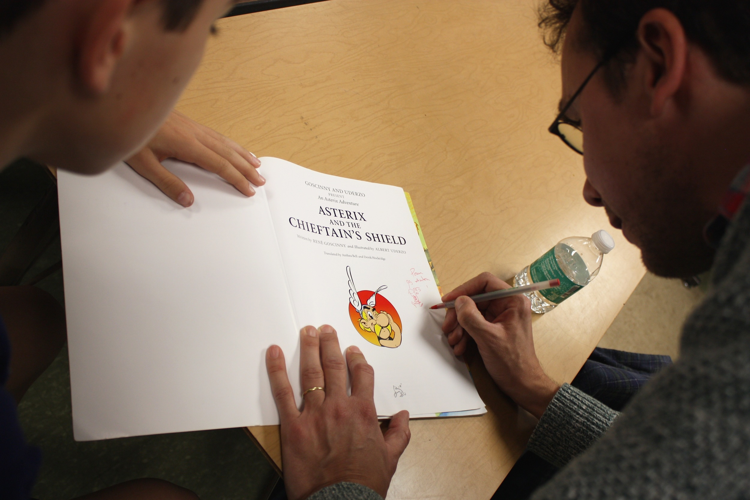 Louis signing a copy of the graphic novel Asterix for a student