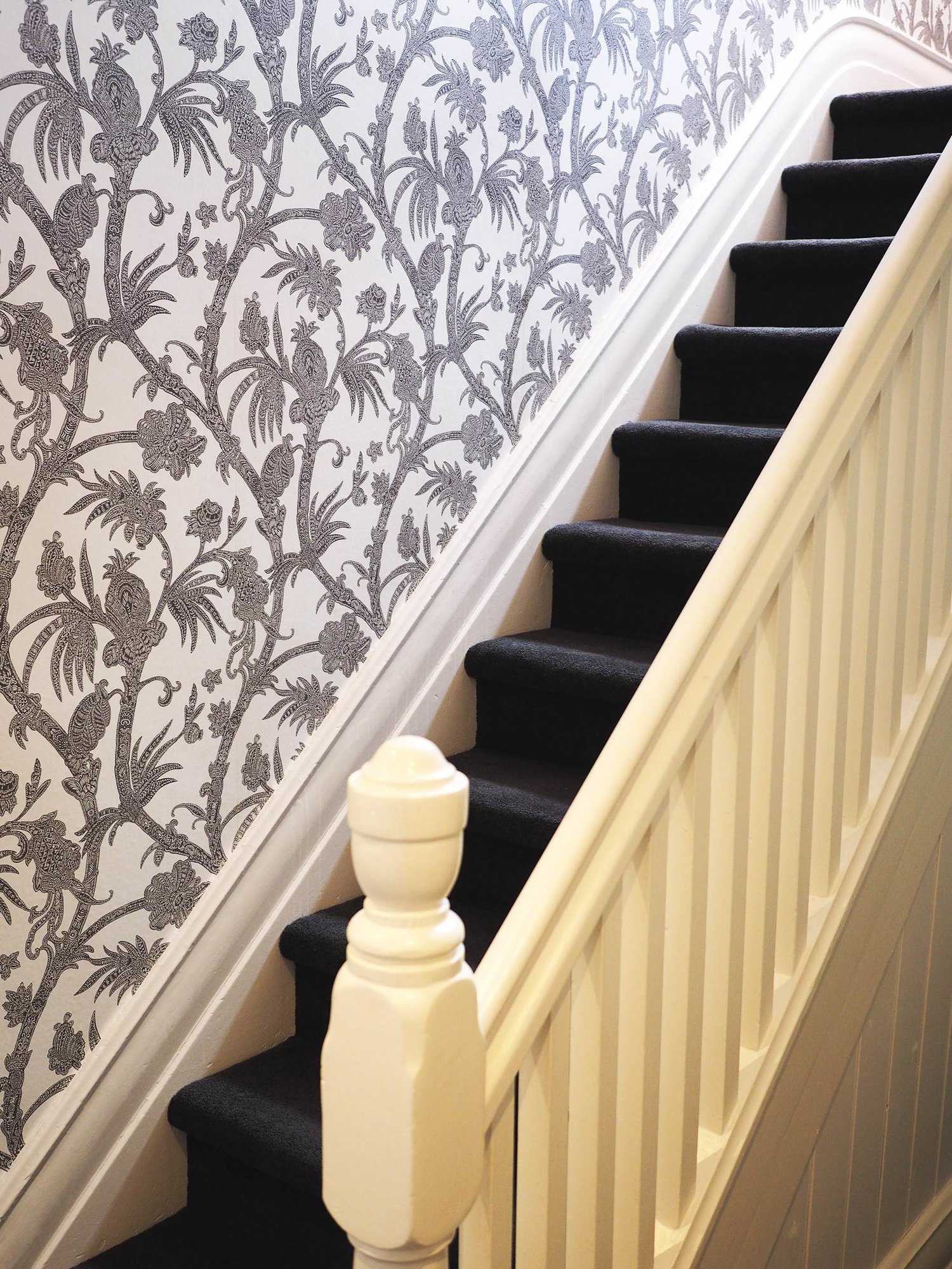up, up, up past dramatic wallpaper twirls - The main bedroom was relocated upstairs to take advantage of the incredible views, so we worked with the original staircase to create a fun journey between upstairs & downstairs. American wallpaper in a monochrome colourway brings in a touch of the botanical setting, in an elegant sweep of twirled leaves & stems.