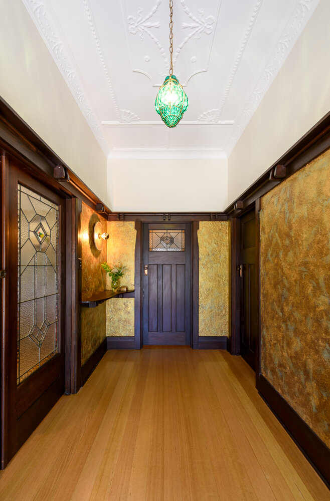 the 'wow' factor starts at the front entry - The lucky discovery of the original plans and specifications (found by the new owner's tenacious hunting) revealed that the entry once had a 'tiffany finish' applied to the walls.Using 21st century paint from Haymes, we re-interpreted this early 20th century finish with carefully applied layers of copper, gold and russet paint by the incredibly talented painter in our team.The result: a room that literally glows, enhancing the original 1929 emerald green glass pendant light, intricate plastered ceilings and richly detailed timber work.