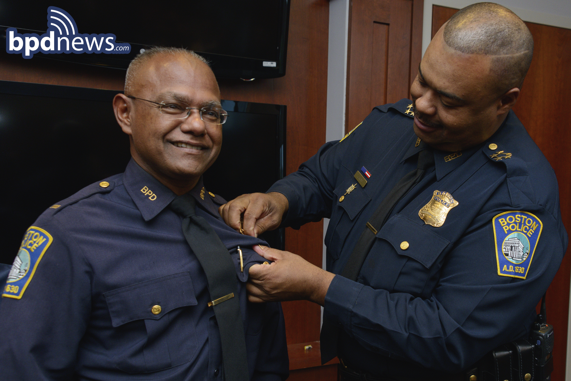 Captain Hosein receives his Captain's BAdge from Chief Gross