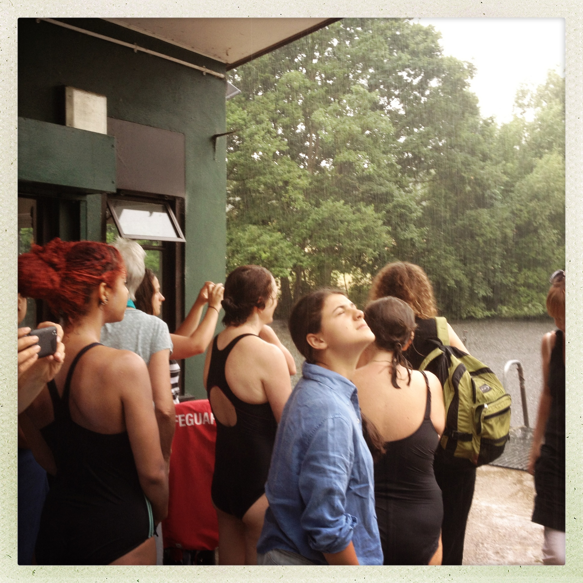 Evacuated swimmers, failing to see irony, huddle under awning to keep dry