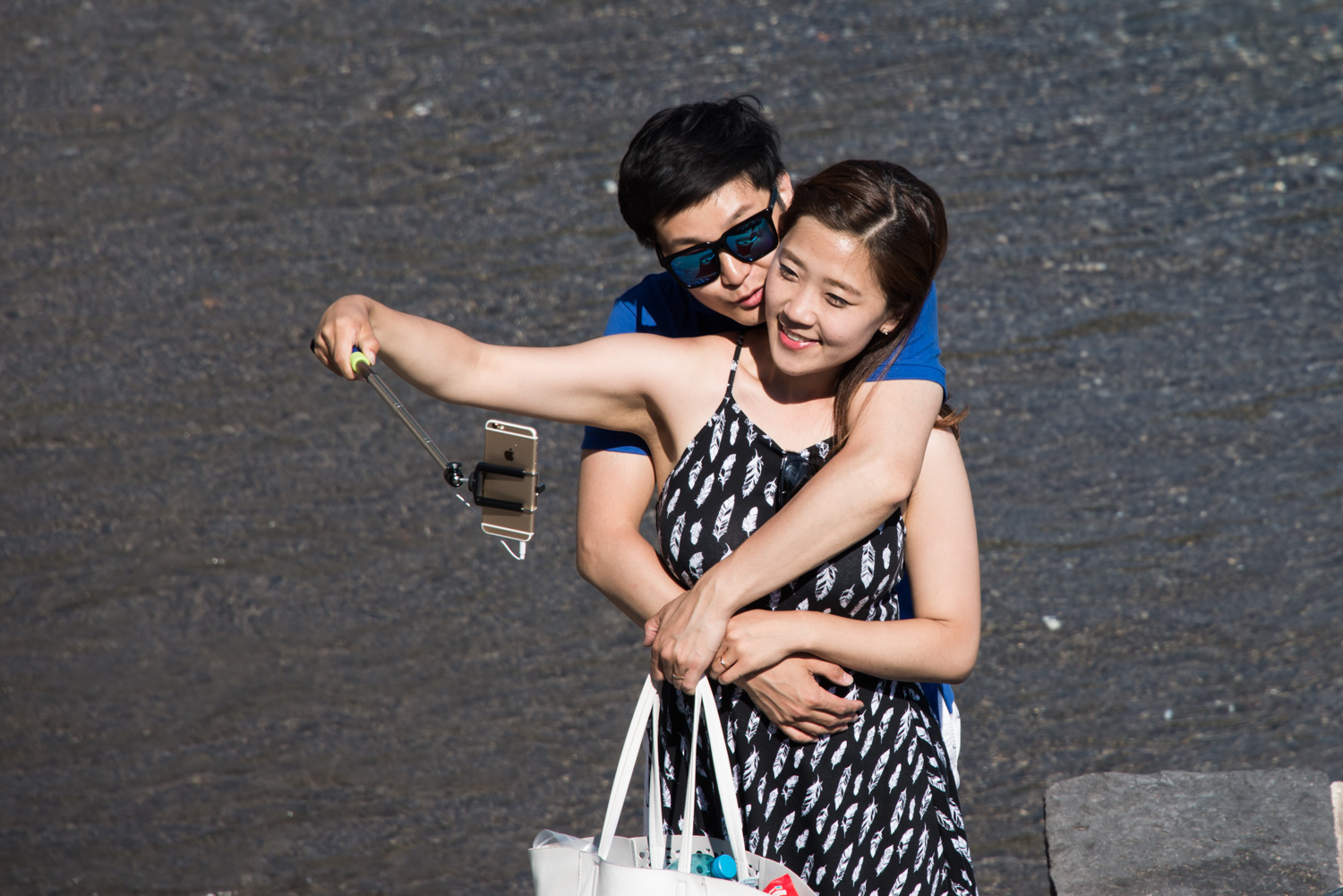 A couple taking a selfie on a beach in Italy