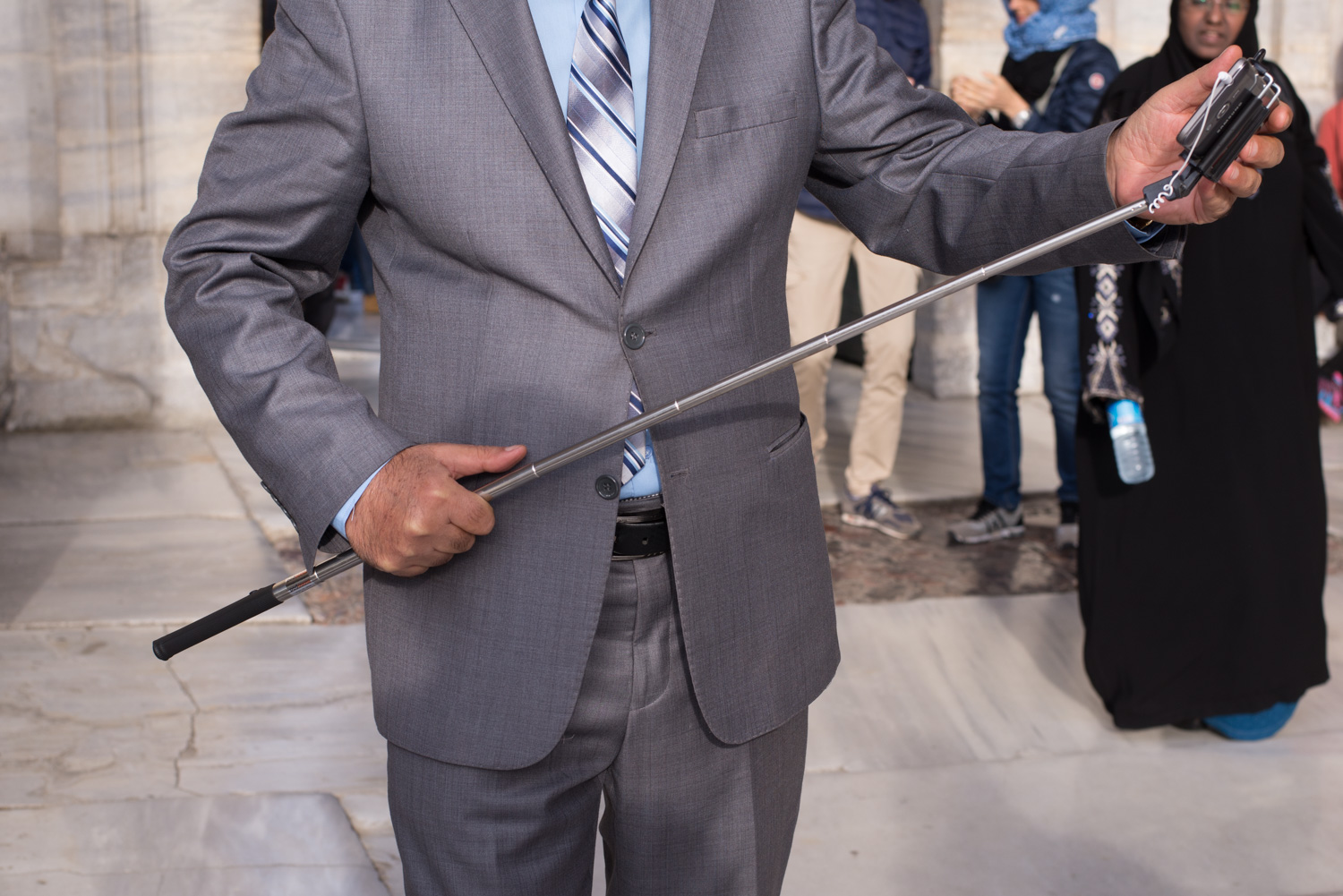 A man in a suit with a selfie stick