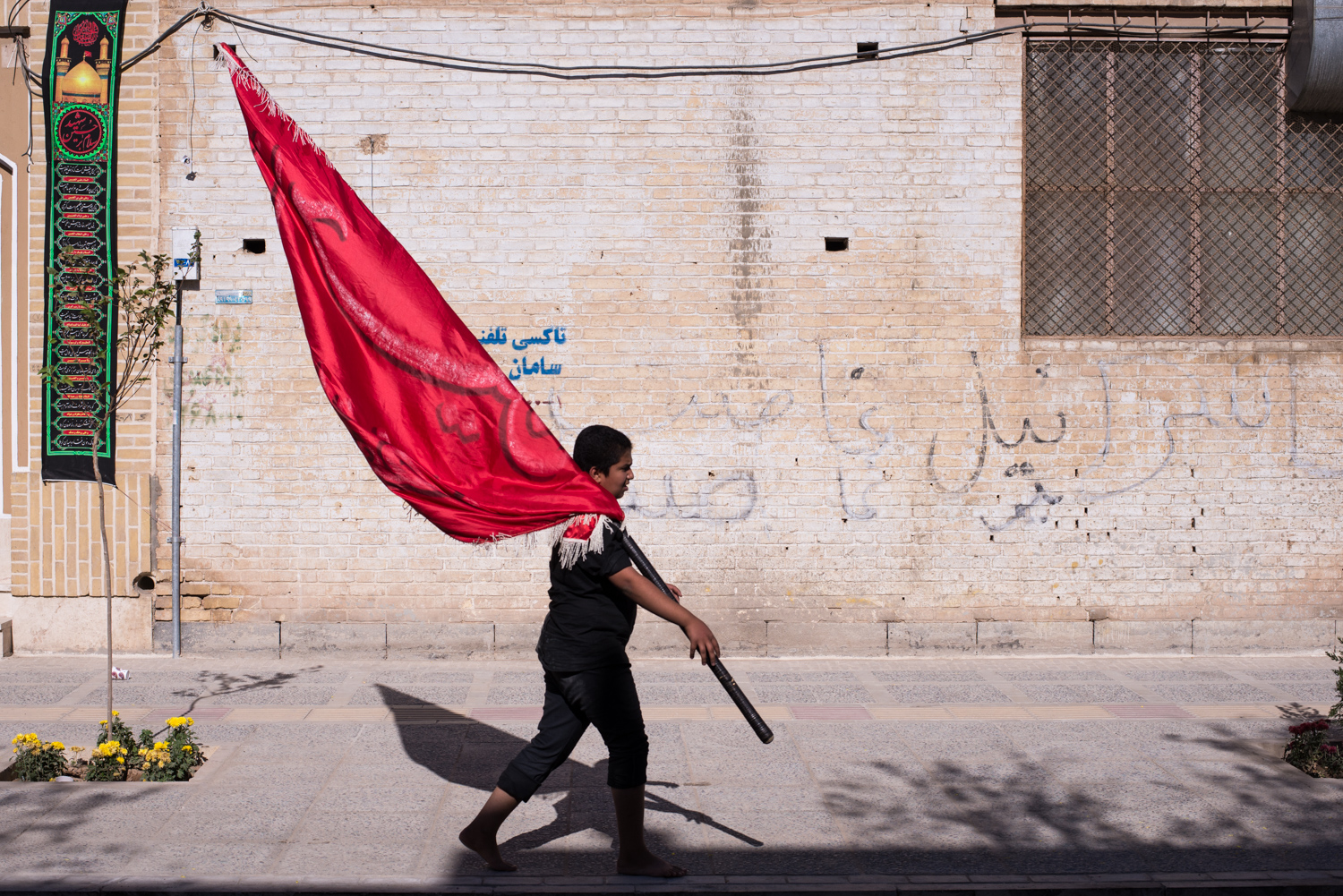 A boy carrying a flag used in an Ashura parade in Yazd, Iran. His concentration reflects the intensity of his involvement in the classic Shia mourning of Hussein.