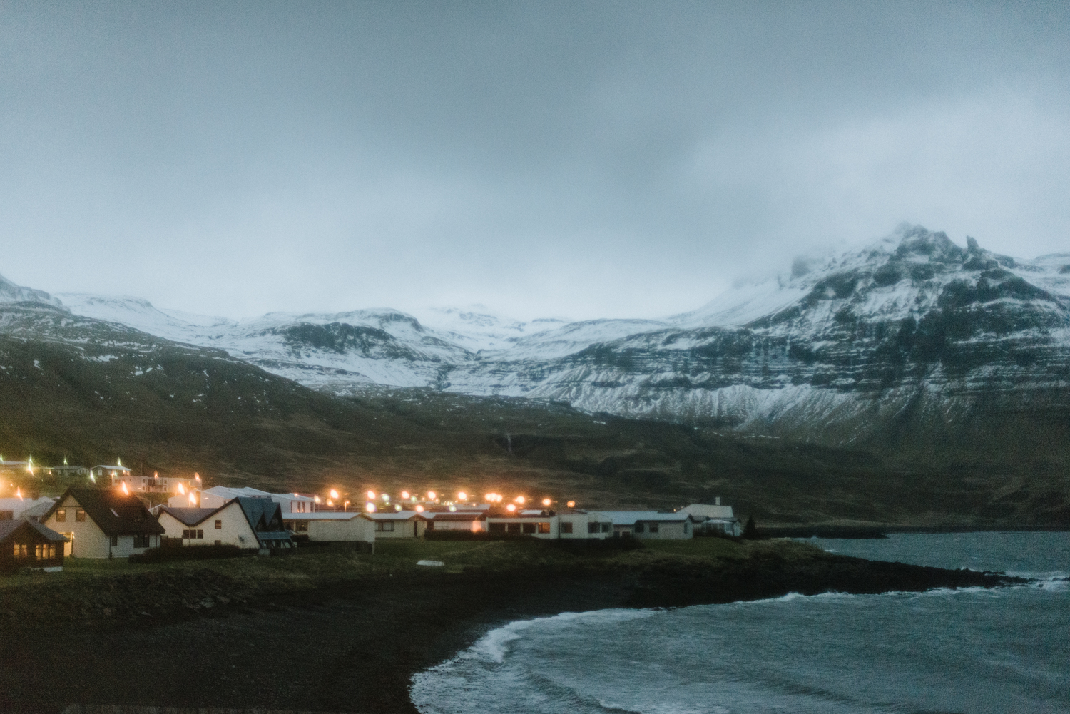 An isolated coastal village shot at dusk with lights on and moun