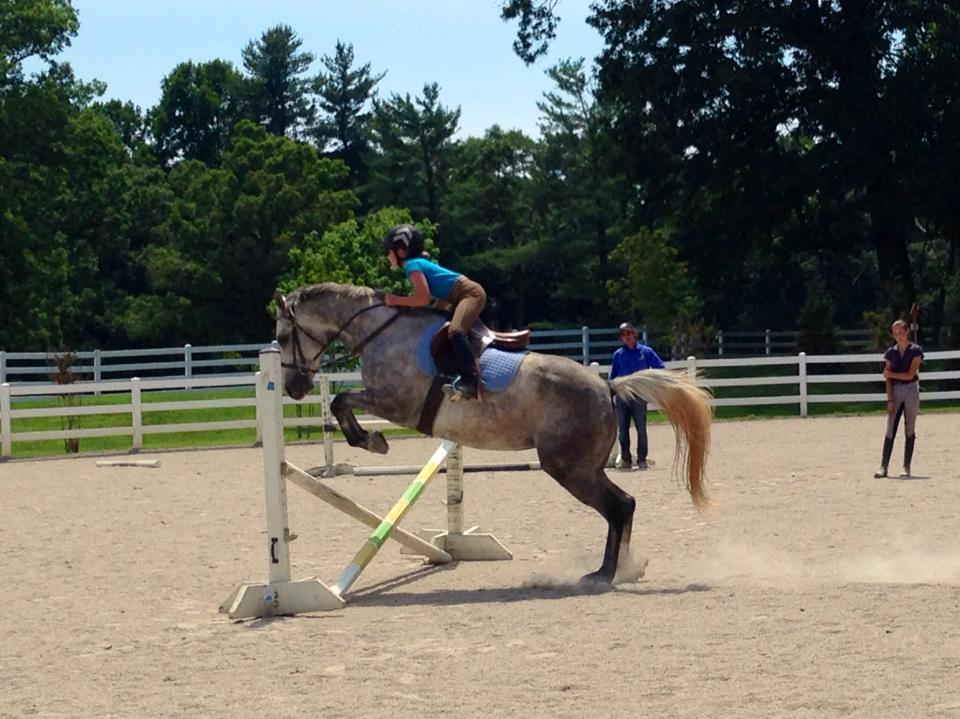 Isabell riding in a jump clinic with Dom Schramm