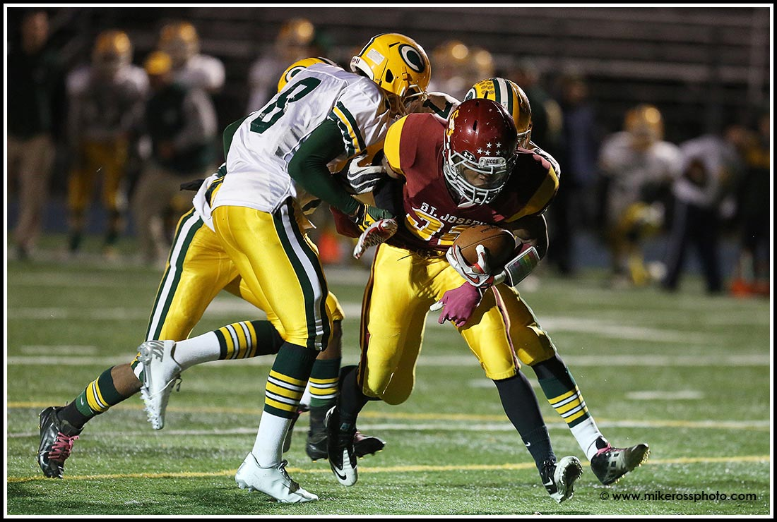 Mike Ross Connecticut freelance -St. Joseph's #32 Mufasa Abdul-Basir drags three Trinity Catholic High School defenders into the endzone for a score during first half action on Thursday evening. St. Joseph would win 49.14.