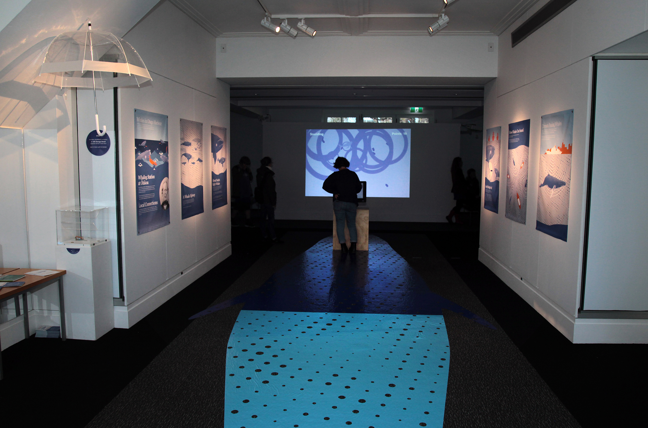 Gallery interior showing vinyl didactics and a video game