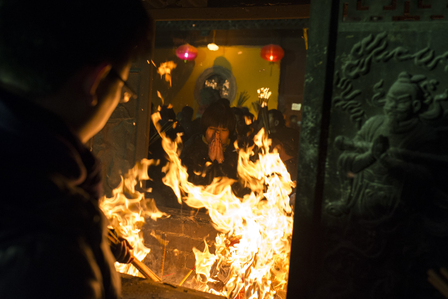 A woman is deep in prayer between the flames at Longhua Temple.