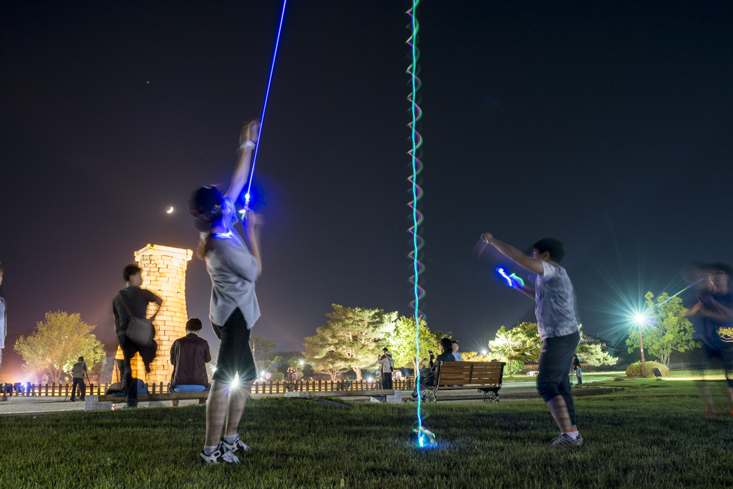 A family is having fun with some glowing helicopter toys. In the background is Cheomseongdae Observatory. Built in the 7th century A.D., it is the oldest surviving observatory in Eastern Asia. The moon is hanging out above the observatory.