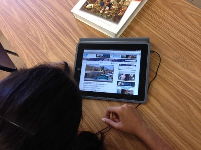 Student listens to French broadcast on an iPad.