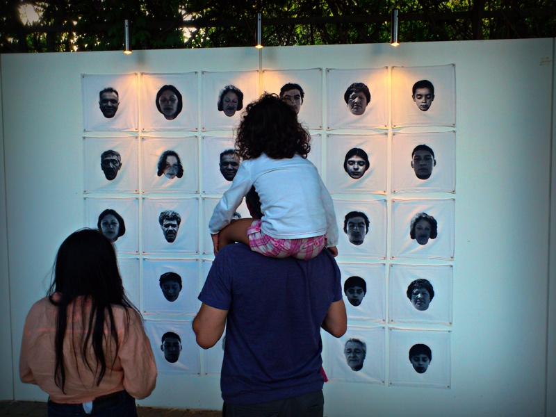 A father and his daughters view one of the installations at a mixed-media art fair in Parque Araucano, Santiago.